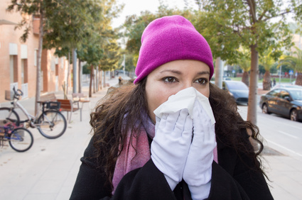 woman with a great cold sneezes with a tissue in her hands